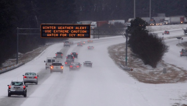 Cars drive under a traffic sign displaying winter storm warnings after a rare snowstorm in Kennesaw, Georgia