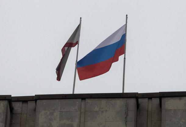 A Russian flag is raised next to a Crimean flag on top of the Crimean parliament building in Simferopol