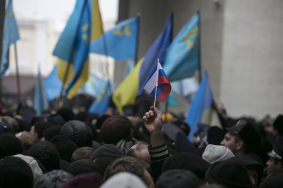 An ethnic Russian Ukrainian holds a Russian flag as Crimean Tatars rally near the Crimean parliament building in Simferopol